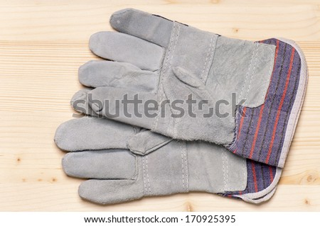 Close up of working gloves against wooden surface - stock photo