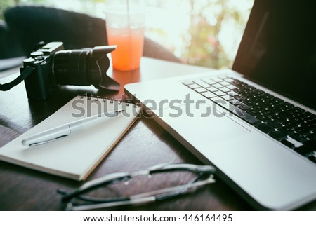 Close-up of working place in office with wooden table and laptop laying on it