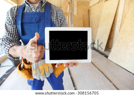 close-up of workman with tablet and thumbs up - stock photo