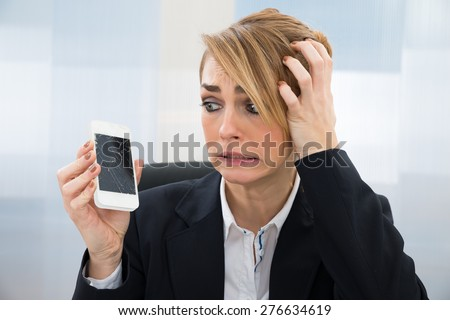Close-up Of Worried Businesswoman Holding Broken Screen Smartphone In Office - stock photo