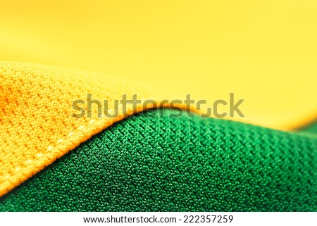 Close up of yellow and green polyester with a neat seam - stock photo