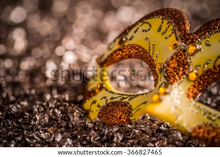 Close up of yellow carnival mask on glittering background - stock photo