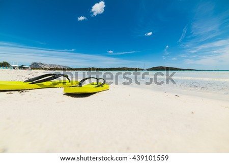 close up of yellow flip flops on the sand - stock photo