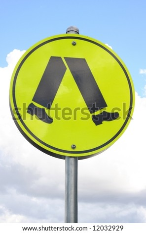 close up of yellow pedestrian walk sign against blue sky background - stock photo