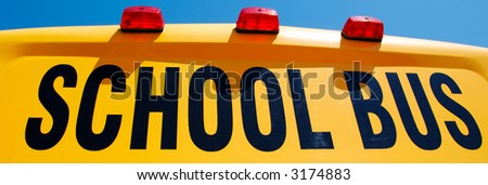 Close up of yellow school bus against bright blue sky - stock photo