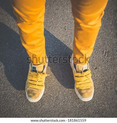 close up of yellow shoes legs of young beautiful hipster woman in the city - stock photo