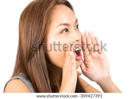 Close up of young, adorable Asian girl with light brown hair telling secret gossip protecting her mouth with hands looking away to side off screen. Thai national of Chinese origin. Horizontal - stock photo