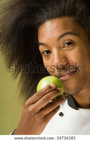 Close Up of Young African America Chef without Hat Holding a Green Apple - stock photo