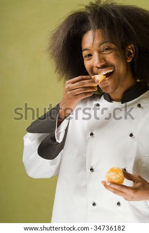 Close Up of Young African American Chef Biting into an Orange - stock photo