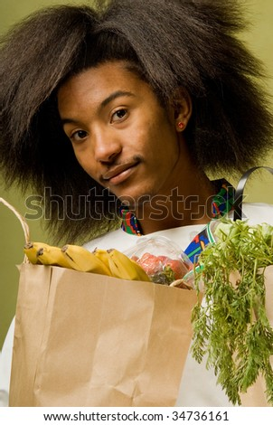Close Up of Young African American Chef holding Brown Paper Bags full of Groceries - stock photo