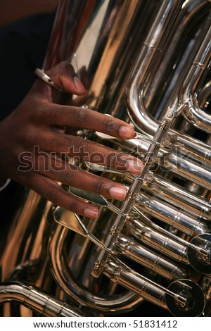 Close-up of young African-American man playing tuba. - stock photo