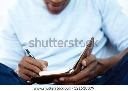 Close-up of young African man writing something in notepad - stock photo
