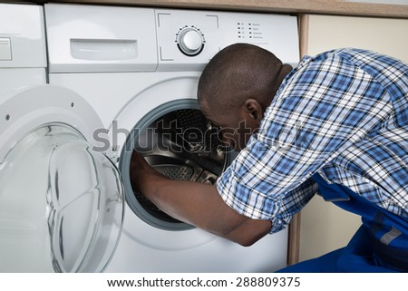 Close-up Of Young African Technician Repairing Washing Machine - stock photo