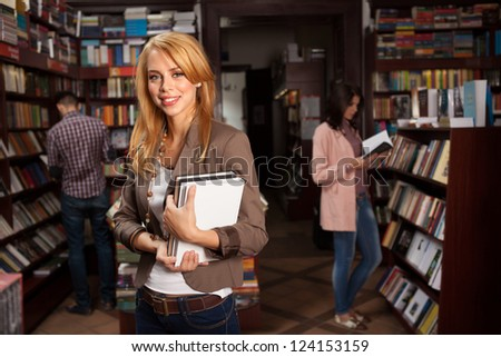 close-up of young attractive caucasian girl in bookshop holding two different colored books in her hands with other people reading books in background - stock photo