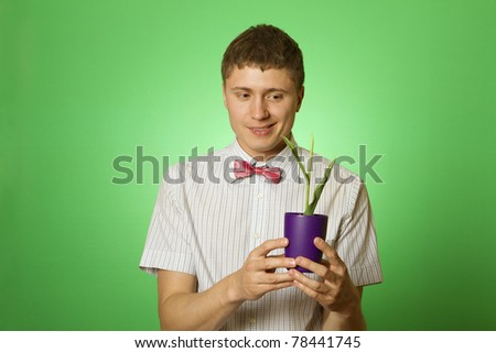 Close-up of young attractive man observes cultivation of young plants - stock photo