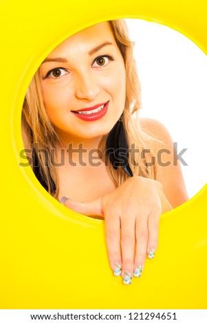Close up of young attractive woman looking through yellow rubber ring. - stock photo