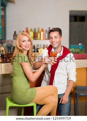 close-up of young beautiful caucasian couple drinking cocktails at the counter in colorful cafe - stock photo