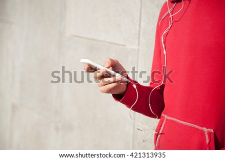 Close-up of young beautiful female hands using phone app while resting after everyday workout. Woman athlete runner taking a break and using smartphone. Copyspace - stock photo