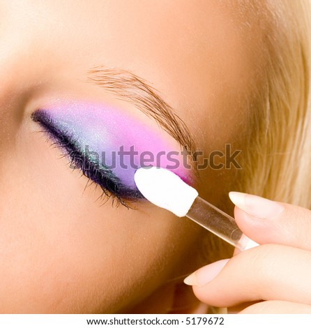 close-up of young beautiful girl make her make-up with brush - stock photo