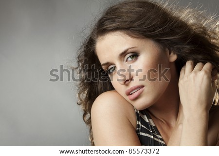 Close-up of young beautiful girl on grey background