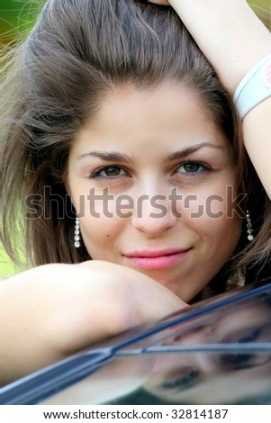 close-up of young beautiful woman (reflection on car) - stock photo