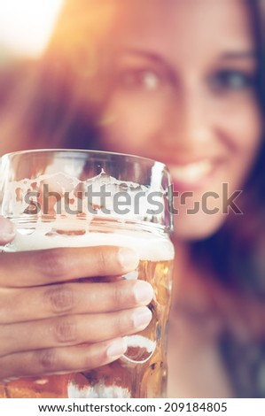 Close-up of young beautiful woman with a glass of beer - stock photo