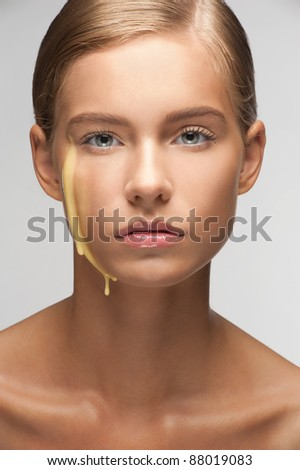 Close-up of young beautiful woman with liquid moisturizing facial cream on her face - stock photo