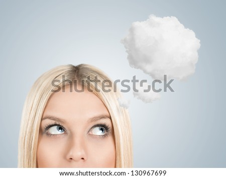 Close up of young blonde woman looking up for thought bubble above her head with copy space - stock photo