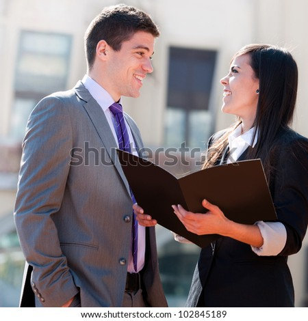 Close up of young business couple with file outdoors. - stock photo