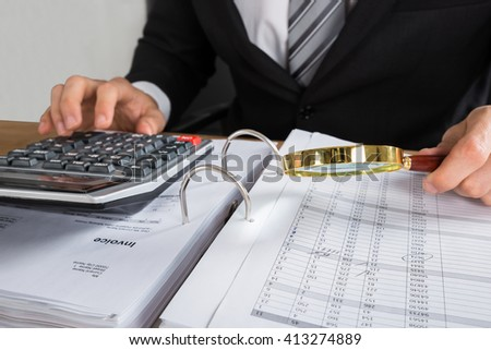 Close-up Of Young Businessman Checking Invoice With Magnifying Glass At Desk