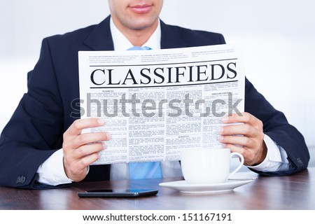 Close-up Of Young Businessman Reading Classifieds On Newspaper - stock photo