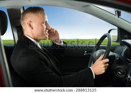 Close-up Of Young Businessman Using Cellphone While Driving