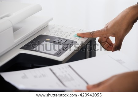 Close-up Of Young Businesswoman Hand Operating Printer In Office - stock photo