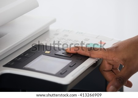 Close-up Of Young Businesswoman Hand Pressing Printer's Button In Office