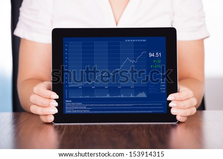 Close-up Of Young Businesswoman Presenting Graph On Digital Tablet - stock photo
