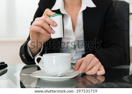 Close-up Of Young Businesswoman Putting Sugar In Cup At Glass Desk - stock photo