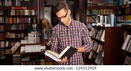 close-up of young caucasian man with eyeglasses in a bookstore with an opened book in his hands reading something with other bookshelves in background - stock photo