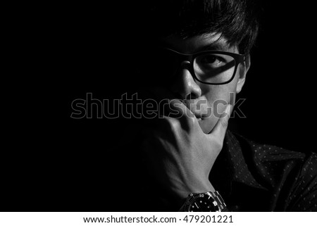 Close-up of young content man pondering, low key, black and white