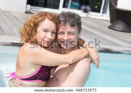 Close-up of young couple cuddling each other near pool on a sunny day