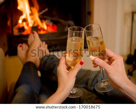 close up of young couple drinking champagne in front of a open wood fire - stock photo