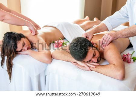 Close up of young couple enjoying simultaneous body massage in spa. Two therapists doing back massage on couple at the same time. - stock photo
