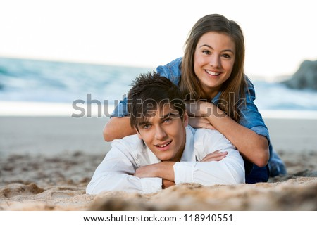 Close up of young couple relaxing on sandy beach. - stock photo