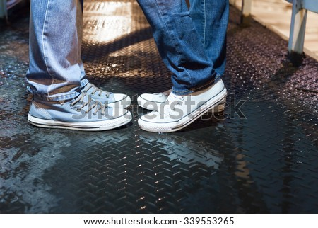 Close up of young couple's feet in a night time setting. Love and relationship concept. - stock photo