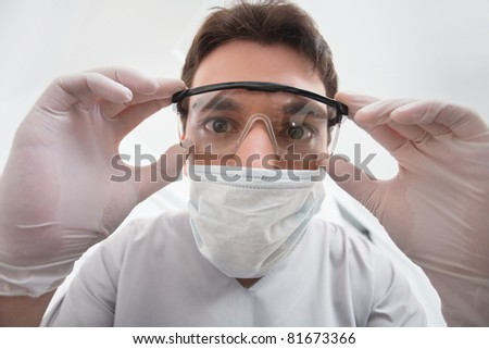 Close-up of young dentist adjusting his eyewear - stock photo