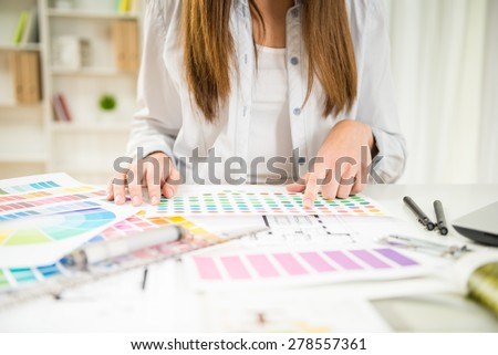 Close-up of young designer working with color samples in her office. - stock photo