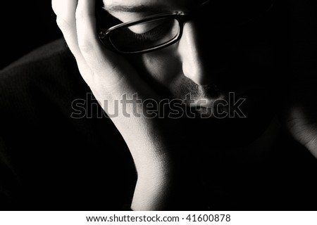 Close-up of young despaired man contemplating, low key, black and white - stock photo