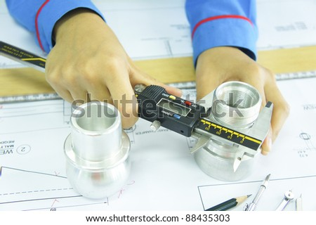 close up of young engineer holding a vernier caliper - stock photo