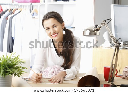 Close-up of young fashion designer working in her studio. - stock photo