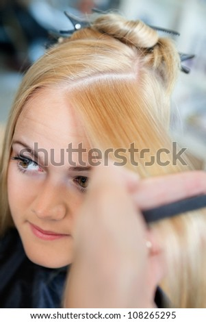 Close up of young female getting a hairdo from hairstylist at salon
