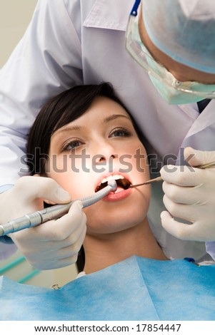 Close-up of young female with open mouth at the dentist office while doctor examining her oral cavity - stock photo